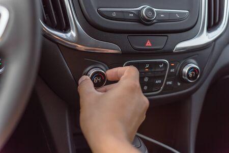 Left hand turning knob on modern car cooling temp adjust to 64 Fahrenheit F degree. Asian male hand on dashboard air conditioner car interior 版權商用圖片