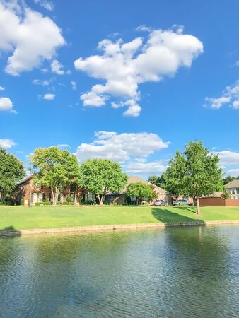 Beautiful waterfront house with row of mature bold cypress trees in suburbs Dallas, Texas, USA. Suburban single family detached home along river with high stone retaining wall, green grass lawn