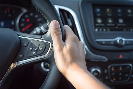 Close-up Asian male hand holding modern car steering wheel with audio control buttons. Voice and Phone buttons are available to make and receive calls hand free. Imagens