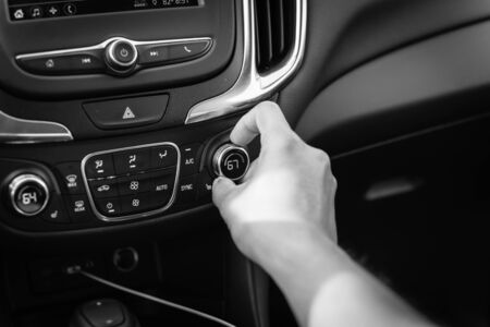 Vintage tone right hand turning knob on modern car cooling temp adjust to 67 Fahrenheit F degree. Asian male hand on dashboard air conditioner car interior 版權商用圖片