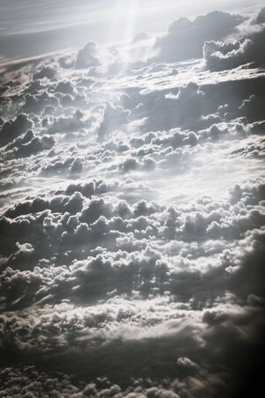 Vintage tone beautiful and unusual Altocumulus or Cirrocumulus cloud formation seen from airplane window at sunrise. Skyline view above the clouds from the air