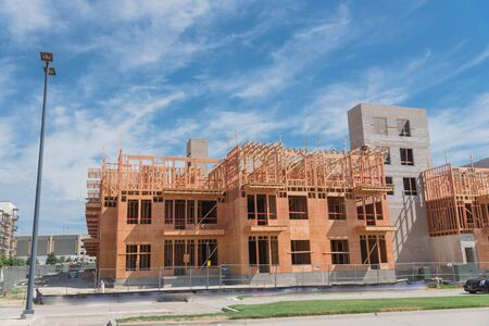 New development mixed neighborhood with wooden condominium under construction, completed apartment complex and commercial buildings. Urban construction site near street blue cloud sky, Dallas, Texas Stock fotó - 132038458