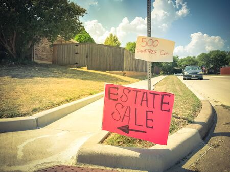 Vintage tone estate sale sign with address at suburban neighborhood near Dallas, Texas, America. Lawn sale sign on the sidewalk near local drive intersection