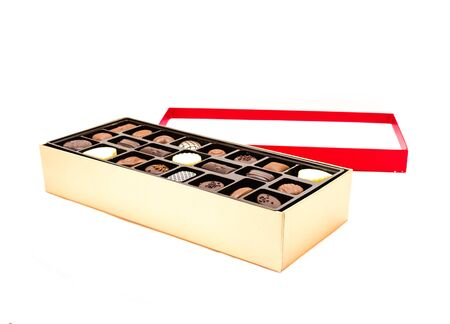 Open chocolate box with variety of truffle isolated on white background. Festive chocolate confectionery for holidays and special events