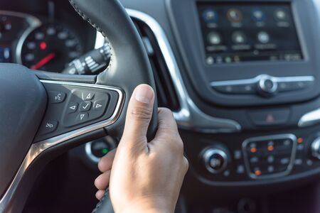 Close-up Asian male hand holding modern car steering wheel with audio control buttons. Voice and Phone buttons are available to make and receive calls hand free. Stock Photo