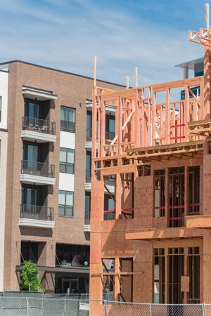 Close-up new development neighborhood with rental units under construction in North Dallas, Texas, USA. Wooden framework of five-story apartment complex with large patio near completed buildings