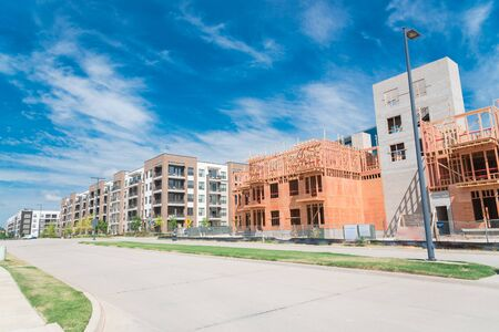 Street side development neighborhood with rental units under construction in North Dallas, Texas, USA. Wooden framework of five-story apartment complex with large patio near completed buildings
