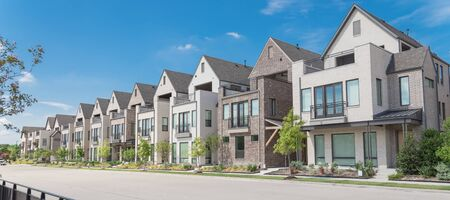 Panorama park side brand new row of three story single family houses in Richardson, North Dallas. Modern design of urban living residences with side private courtyards near large street and fence