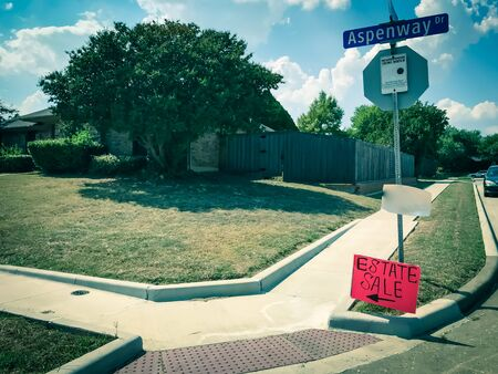 Red estate sale sign with blank copy space for address at suburban neighborhood near Dallas, Texas, America. Lawn sale sign on the sidewalk near local drive intersection