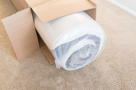 Close-up top view roll-packed spring mattresses unbox on carpet floor background