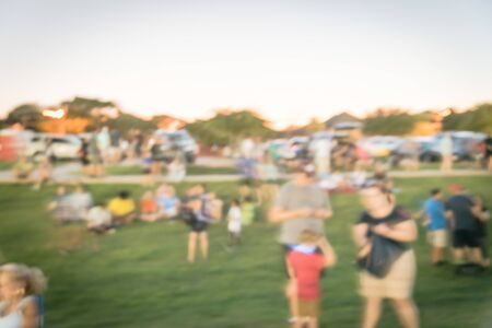 Abstrakte verschwommene riesige Gruppe verschiedener Menschen besucht Sommerveranstaltung im Stadtpark in der Nähe von Dallas, Texas, Amerika. Eine Gruppe von Familienmitgliedern genießt ein öffentliches Festival bei Sonnenuntergang mit Bokeh-Beleuchtung