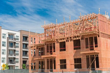 Close-up new development neighborhood with rental units under construction in North Dallas, Texas, USA. Wooden framework of five-story apartment complex with large patio near completed buildings Stock fotó - 132038197