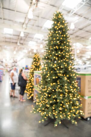 Blurry background customer shopping for giant artificial Christmas tree at wholesale store in Texas