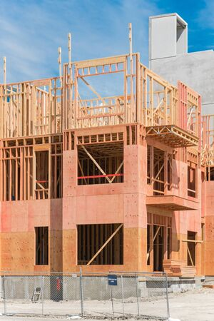 Close-up of multistory condominium under construction with wooden lumber timber framework and concrete elevator shaft. Modern apartment complex rental living space construction area near Dallas, Texas