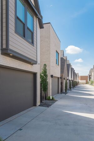 Row of garages from modern three story houses in North Dallas, Texas. Large back alley of new development residential community with metal fence gate and well trim landscape