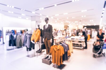Blurred image of mannequins inside a men fashion store with unidentified customers walk out. Abstract blurred of shopping mall boutique interior, men clothes shop with bokeh light background.