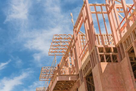 Low angle view of modern condominium building with large patio under construction near North Dallas, Texas, America. Wooden house with timber framing, truss, joist, beam close-up under cloud blue sky Archivio Fotografico