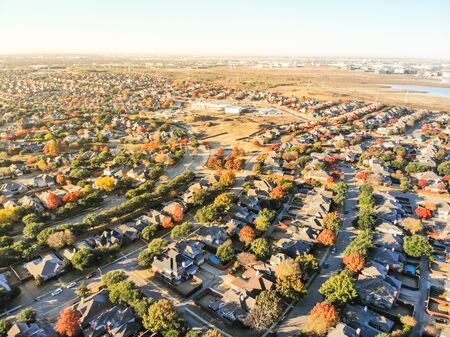 Aerial view suburban sprawl row of single-family detached house on large expanses of land Dallas, Texas. North Lake, warehouses from industrial zone in distance. Urban areas of housing fall landscape