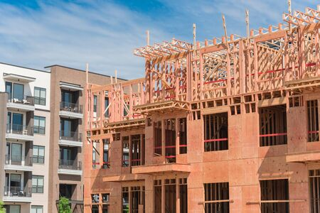 Close-up new development neighborhood with rental units under construction in North Dallas, Texas, USA. Wooden framework of five-story apartment complex with large patio near completed buildings Stock fotó - 132039112