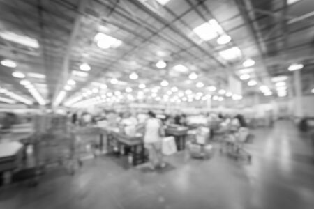 Vintage tone blurred motion long line of customers at check-out counter in America. Concept of busy shoppers waiting at wholesale store during weekend