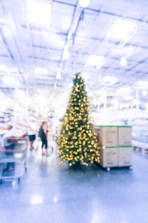 Blurred huge Christmas trees decoration in wholesale store. Wreaths and strings of bokeh lights surround the artificial Christmas tree. Xmas decorations displayed for selling in USA. Customer shopping