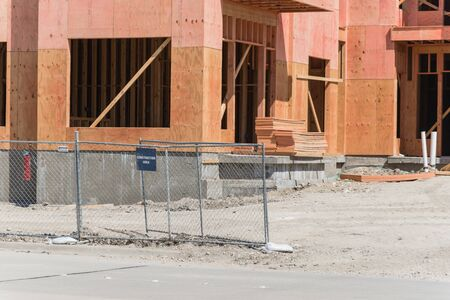Close-up construction site with temporary metal fence of condominium building near Dallas, Texas, USA. Wooden framework of luxury urban apartment complex with large concrete slab foundations