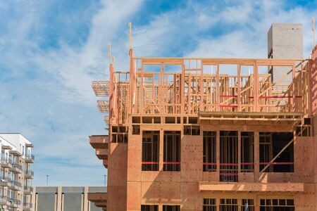Wooden timber framework of apartment complex under construction new completed buildings. Luxury condominium with multilevel garage near Dallas, Texas