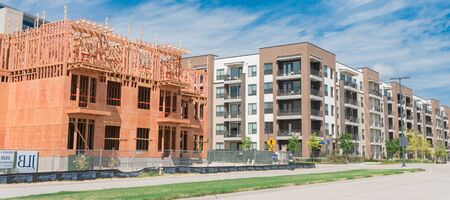 Panorama view street side development neighborhood with rental units under construction in North Dallas, Texas, USA. Wooden framework of five-story apartment large patio near completed buildings 写真素材