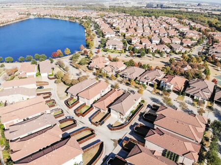 Aerial view urban sprawl with row of new modern houses and city building in background. Row of brand new two stories single-family detached homes with wooden fence backyard and colorful autumn leaves