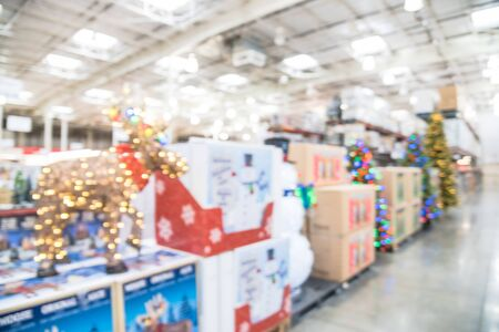 Blurred image LED lighted deer, pop up led snowman and huge Christmas trees decoration in wholesale store. Wreaths and strings of bokeh light surround the artificial Christmas tree. Xmas display in US
