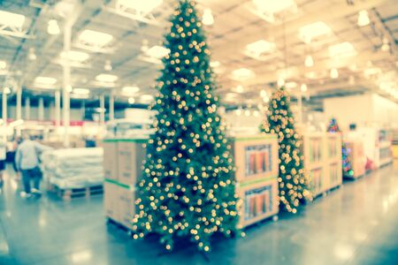 Blurred huge Christmas trees decoration in wholesale store. Wreaths and strings of bokeh lights surround the artificial Christmas tree. Xmas decorations displayed for selling in USA. Customer shopping Banco de Imagens - 132039900