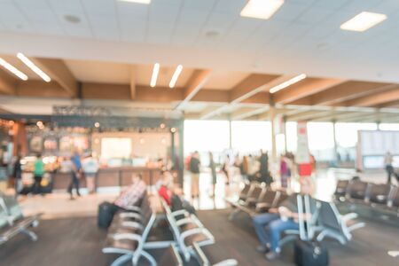 Blurred image people waiting in terminal gate near coffee shop at American airport. Traveler with baggage sitting on armchair and long queue of crowded with bokeh light
