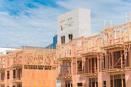 Close-up of multistory condominium under construction with wooden lumber timber framework and concrete elevator shaft. Modern apartment complex rental living space near Dallas, Texas