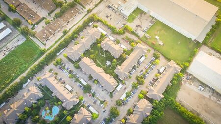 Panorama aerial view apartment building complex near large industrial and warehouse building in Houston, Texas, USA. Top of rental units with swimming pool and outdoor parking lots 写真素材