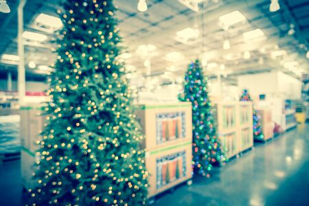 Blurred image huge Christmas trees decoration in wholesale store. Wreaths and strings of bokeh lights surround the artificial Christmas tree. Xmas decorations cheerful displayed for selling in America Banco de Imagens - 132039773