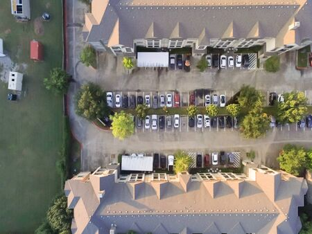 Top view apartment building complex near vacant land with containers at sunset in Houston, Texas, USA. Top of rental units property with swimming pool and outdoor parking lots