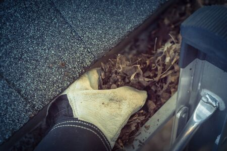 Close-up man hand with gloves on ladder cleaning house gutter from leaves and dirt. Roof gutter cleaning near shingles roof in summer time Фото со стока