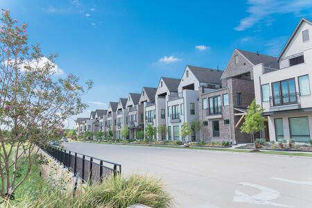 Park side brand new row of three story single family houses in Richardson, North Dallas location. Modern design of urban living residences with side private courtyards near large street with fence