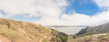 View from Golden Gate Observation Deck to the red bridge and downtown San Francisco in foggy summer day. Panorama ocean view near Hawk Hill with steep hillside road and open bay. Stock fotó