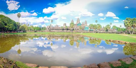 Panorama lakeside Angkor Wat facade under construction and palm tree reflection under summer cloud blue sky with unidentified tourists. A temple complex in Cambodia, world largest religious monument