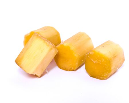 Four organic sugar cane cuts isolated on white background. Piece of fresh peel chopped sugar cane sticks chunks with clipping path and copy space