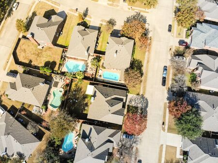 Straight down view of upscale pool houses residential neighborhood in Dallas suburbs with colorful fall foliage. Large detached home permanent dwelling, new roof shingle, parked cars on street, drive way