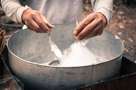 Asian hand rolling cotton candy in floss machine using bamboo stick and long spoon in Vietnam. Process of street food making