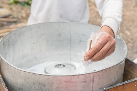 Close-up Asian hand rolling cotton candy in floss machine in Vietnam. Process of street food making