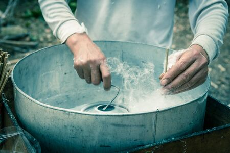 Vintage tone close-up Asian hand rolling cotton candy in floss machine in Vietnam. Process of street food making Stock Photo