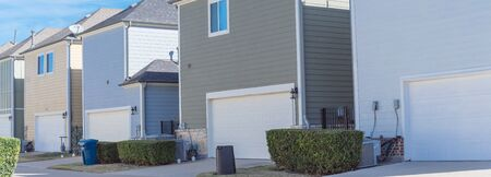 Panoramic back alley of residential neighborhood line of two-car garage door colorful houses near Dallas Stock Photo