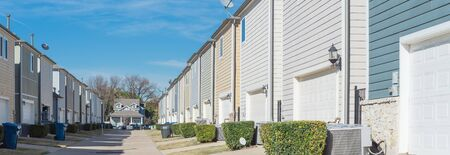 Panoramic back alley of residential neighborhood line of two-car garage door colorful houses near Dallas