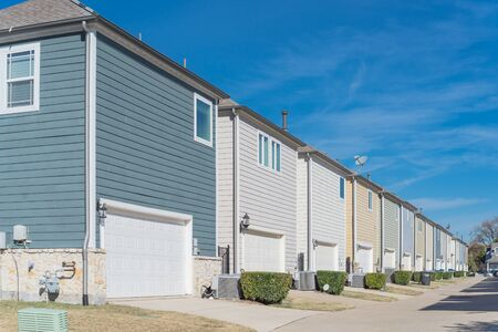 Large corner house and back alley of residential area line of two-car garage door near Dallas