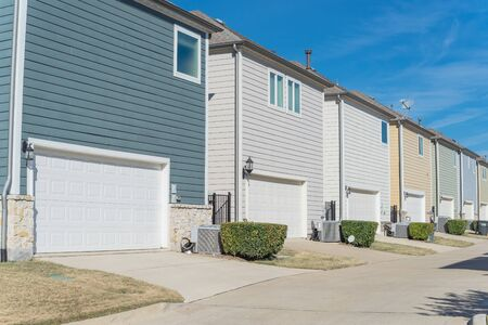 Concrete back alley of residential neighborhood line of two-car garage door colorful houses near Dallas Stock Photo