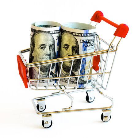 Studio shot empty tiny shopping cart with hundred (100) dollars banknotes inside